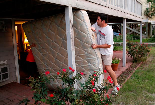 Dean Legge (R) helps his sister-law Josey Vereen (L) remove a mattress at her beachfront home along Waccamaw Drive in anticipation of Hurricane Matthew in Garden City Beach, South Carolina, U.S. October 4, 2016. REUTERS/Randall Hill