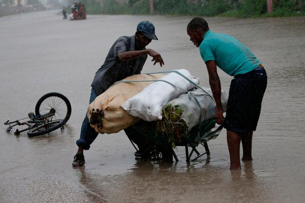 Men attempt to push a wheelbarrow across a flooded street while Hurricane Matthew passes through Port-au-Prince, Haiti, October 4, 2016. REUTERS/Carlos Garcia Rawlins