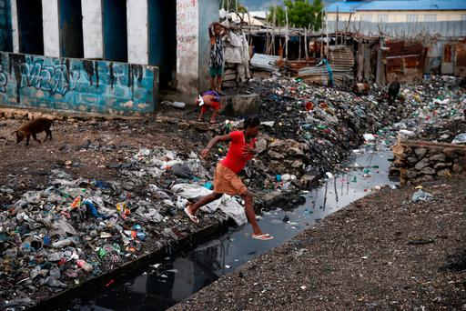 A woman crosses over a water canal after Hurricane Matthew passes Cite-Soleil in Port-au-Prince, Haiti, October 5, 2016