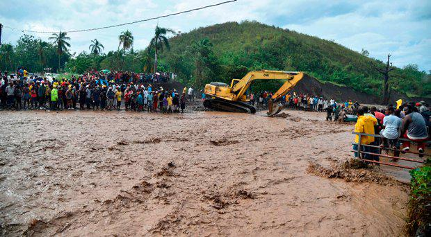 Haitians wait to cross the river La Digue in Petit Goave where the bridge collapsed during the rains of the Hurricane Matthew, southwest of Port-au-Prince, October 5, 2016