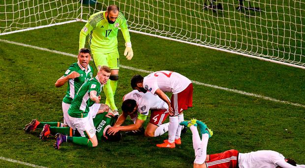 Players rush to Robbie Brady's aid as the Ireland player lies injured after a clash of heads during last night's Group D clash. Photo: Stephen McCarthy/Sportsfile