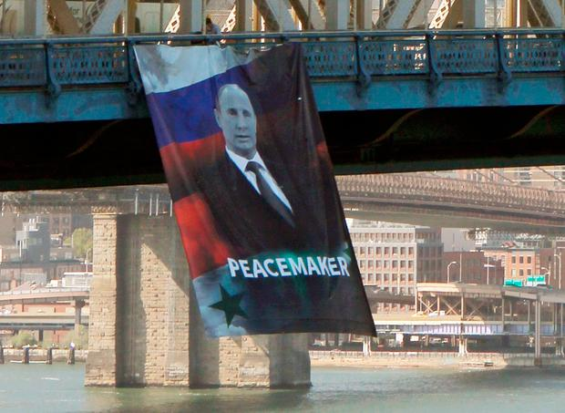 A banner bearing an image of Russian President Vladimir Putin showing him with a Russian and Syrian flag as backdrop and labeling him a