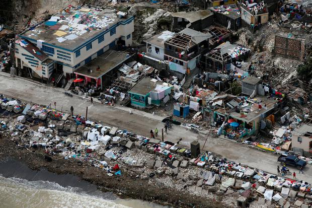 People walk next to destroyed houses after Hurricane Matthew hit Jeremie, Haiti. Photo: Reuters