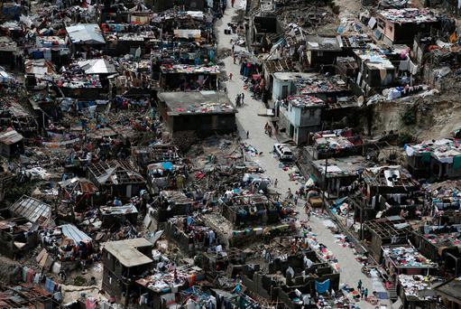People walk on a street next to destroyed houses after Hurricane Matthew hit Jeremie, Haiti. Photo: Reuters