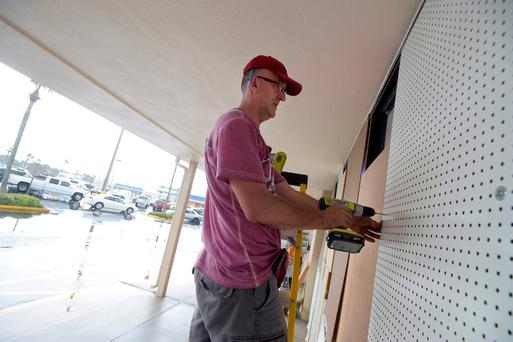 Elijah Nadr boards up the outside of Sunshine Liquor before the arrival of Hurricane Matthew in South Daytona, Florida