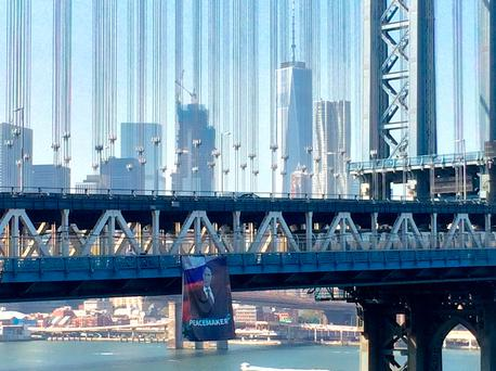 A banner with an image of Russian President Vladimir Putin hangs from the Manhattan Bridge in New York City
