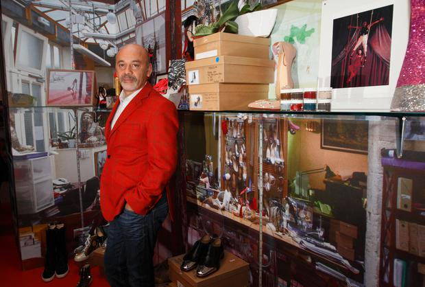 French shoe designer Christian Louboutin poses for a picture at a preview of an exhibition by showcasing 20 years of the famous red-soled shoes at the Design Museum in London