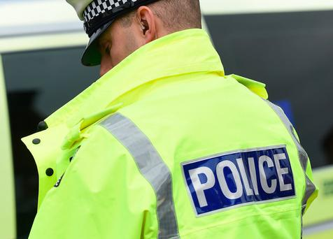A suburban road has been sealed off following reports of a woman brandishing a gun in the street.