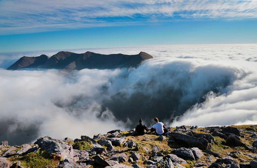 SITTING PRETTY: Lunch above the clouds on the summit of Carrauntoohil, on the MacGillycuddy's Reeks, Ireland's highest mountain range with Rachel O'Toole and Peter Slattery. Photo: Valerie O'Sullivan