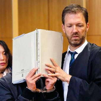 A 16-year-old South Korean covers his face in a court in Frankfurt, Germany,. He is accused of murder following the death a 41-year-old woman in an apparent exorcism ritual in a room in a Frankfurt hotel. At right his lawyer Thorsten Fuchs. (AP Photo/Michael Probst)