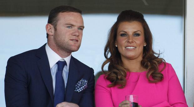 LIVERPOOL, ENGLAND - APRIL 12: Manchester United football player Wayne Rooney and his wife Coleen watch the racing during the first day of the Aintree Grand National meeting on April 12, 2012 in Aintree, England. The first day, known as Liverpool Day, celebrates the city's link with the famous Aintree Racecourse. (Photo by Christopher Furlong/Getty Images)