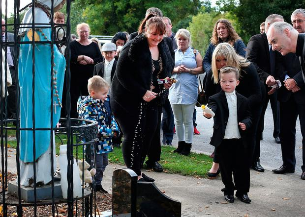 Thomas Connors sprinkles holy water at the shrine to the five adults, five children and one unborn baby who died in the blaze. Photo: Steve Humphreys