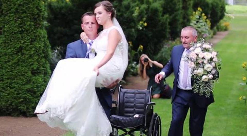 Stuart Patterson carries bride Hannah to the altar