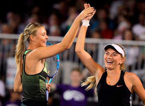 Tennis players Maria Sharapova(L) and Taylor Johnson(R) hi-five during competition in the World TeamTennis Smash Hits charity tennis event benefiting the Elton John AIDS Foundation at Caesars Palace on October 10, 2016 in Las Vegas, Nevada. / AFP PHOTO / John GURZINSKIJOHN GURZINSKI/AFP/Getty Images