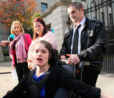 Solicitor Joice Carthy (Pink Jacket and scarf) pictured speaking to the media after the High Court approved a €6m damages award for Nadine Wilkin (in Wheelchair) Pic: Courts Collins