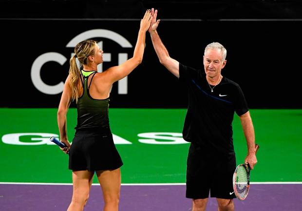 Maria Sharapova) and John McEnroe high-five during their charity match in Las Vegas. Photo by Ethan Miller/Getty Images