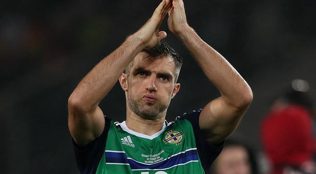 Aaron Hughes applauds the fans at the end of the match (Photo by Matthew Ashton - AMA/Getty Images)