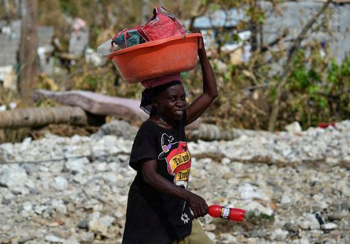 A woman carries her belongings in Jeremie, Haiti. Photo: Getty Images