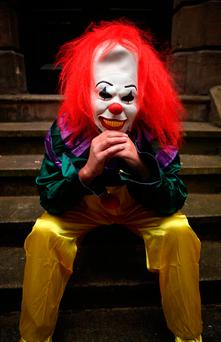 A person wearing a clown costume in a street in Liverpool. The
