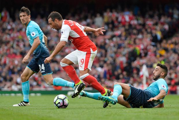 Arsenal's Santi Cazorla evades a challenge from Swansea City's Neil Taylor. Picture: Reuters