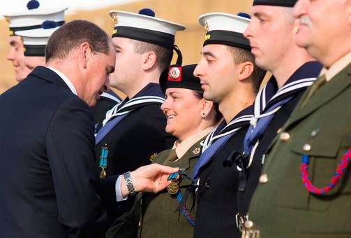 Defence Minister Paul Kehoe presents the medal to Pte Sonya Larrigan from Dundalk, the only female crew member of the LE Eithne during the humanitarian mission rescuing migrants in the Mediterranean. Photo: Mary Browne