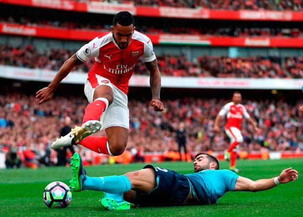 Theo Walcott of Arsenal is tackled by Jordi Amat of Swansea City. Photo by Julian Finney/Getty Images