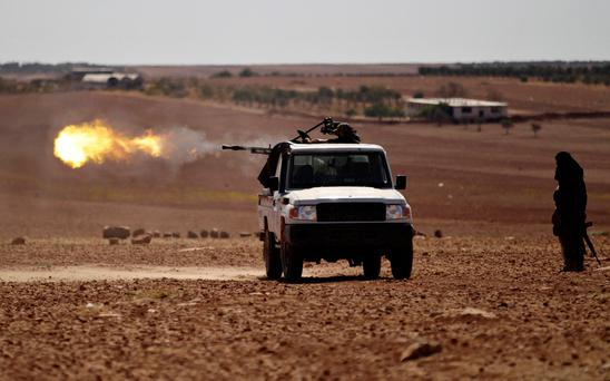 Rebel fighters shoot their weapon towards Dabek town in northern Aleppo countryside, Syria. REUTERS/Khalil Ashawi