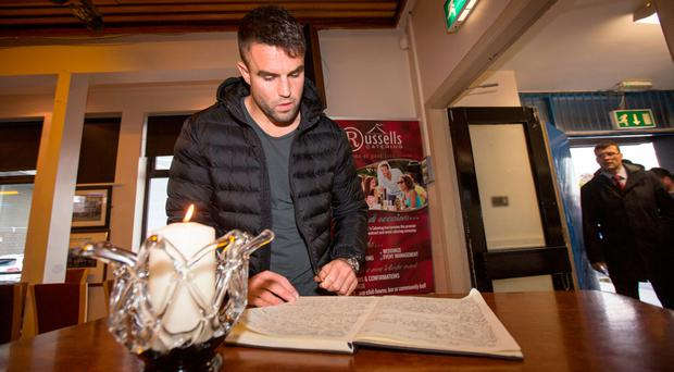 Munster player Conor Murray signs a book of condolence in memory of Anthony Foley at Thomond Park. Photo: Mark Condren