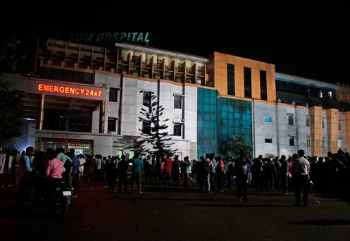 People gather outside the private Sum Hospital after a fire broke out in its intensive care unit, in Bhubaneswar, in the eastern Indian state of Orissa (AP Photo)