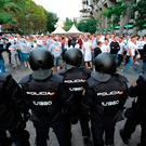 Riot police watch over Legia Warszaw fans outside the Santiago Bernabeu