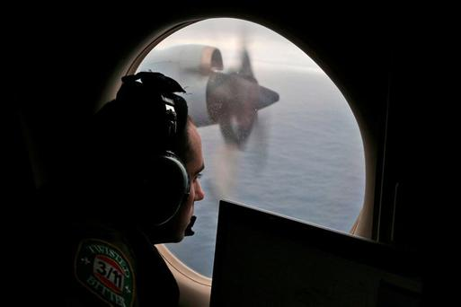 FFlight officer Rayan Gharazeddine scans the water in the southern Indian Ocean off Australia from a Royal Australian Air Force AP-3C Orion during a search for the missing Malaysia Airlines Flight MH370 in 2014. Picture: AP Photo/Rob Griffith