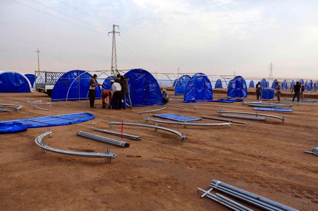 Workers set up a camp for displaced Iraqis in Khazer, Iraq, Wednesday, Oct. 19, 2016. . (AP Photo/Khalid Mohammed)
