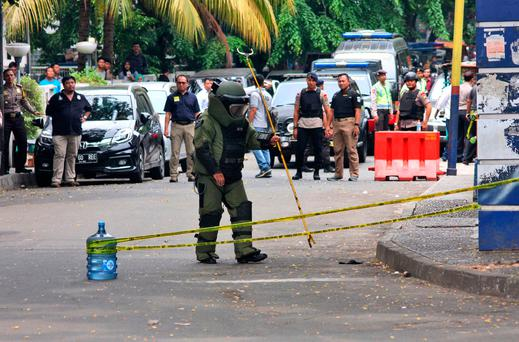 A member of police bomb squad inspects the site where police officers were attacked earlier, in Tangerang, Indonesia (AP Photo)