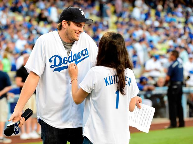 Ashton Kutcher and wife Mila Kunis annouce the Los Angeles Dodgers starting lineup before game four of the National League Championship Series against the Chicago Cubs at Dodger Stadium on October 19, 2016 in Los Angeles, California. (Photo by Harry How/Getty Images)