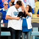 Ashton Kutcher and wife Mila Kunis on the field after they announced the Los Angeles Dodgers starting lineup before game four of the National League Championship Series againt the Chicago Cubs at Dodger Stadium on October 19, 2016 in Los Angeles, California. (Photo by Harry How/Getty Images)