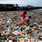 Children take advantage of the gloomy weather to collect washed up rubbish brought by crashing waves due to strong winds of Super Typhoon Haima, local name Lawin, which they will sell at junk shops along the coastal areas, in metro Manila, Philippines October 20, 2016. REUTERS/Romeo Ranoco