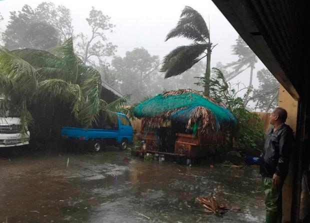A man takes cover as strong winds and rain topple trees while Typhoon Haima lashes Narvacan, Ilocos Sur, northern Philippines on Thursday Oct. 20, 2016.(AP Photo/Bullit Marquez)