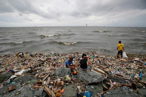 Filipinos scavenges for recyclable materials from the trash that was washed ashore by strong waves brought about by Typhoon Haima in Manila, Philippines, Thursday, Oct. 20, 2016. (AP Photo/Aaron Favila)