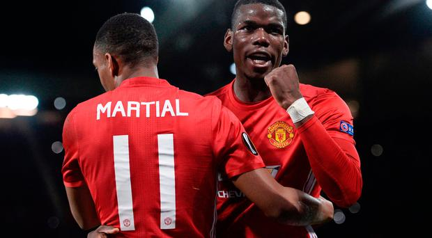 Manchester United's French striker Anthony Martial (L) embraces Manchester United's French midfielder Paul Pogba (R) as he celebrates scoring their second goal from the penalty spot during the UEFA Europa League group A football match between Manchester United and Fenerbahce at Old Trafford in Manchester, north west England, on October 20, 2016. / AFP PHOTO / OLI SCARFFOLI SCARFF/AFP/Getty Images