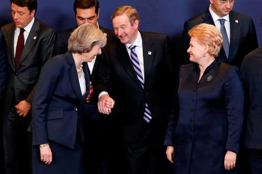 UK Prime Minister Theresa May greets Enda Kenny as Lithuania's President Dalia Grybauskaite looks on as they pose for a family photo at the EU leaders' summit in Brussels. Photo: Reuters