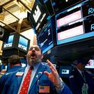 Specialist trader Peter Giacchi gives a price, just before the opening bell, for US cigarette maker Reynolds American Inc. at the post where it is traded on the floor of the New York Stock Exchange