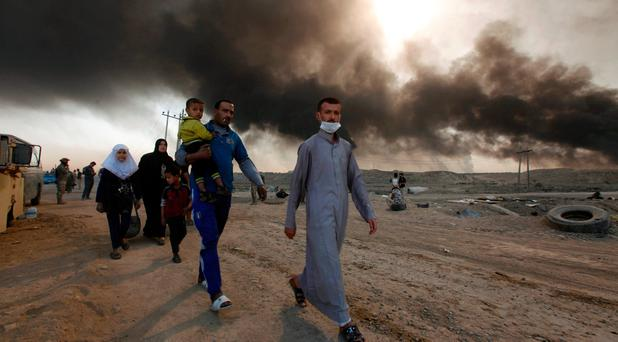 Civilians return to their village after it was liberated from Islamic State militants, south of Mosul in Qayyara, Iraq, October 22, 2016. The fumes in the background are from oil wells that were set ablaze by Islamic State militants. REUTERS/Alaa Al-Marjani