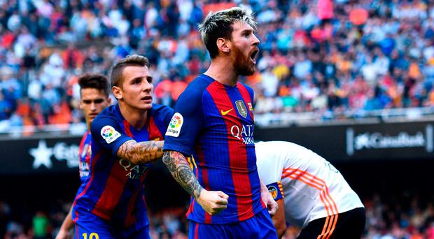 Lionel Messi of FC Barcelona celebrates with his team mates as Neymar Jr. and Luis Suarez reacts on the pitch after being hit by objects thrown from the seats after scoring his team's third from the penalty spot during the La Liga match between Valencia CF and FC Barcelona at the Mestalla