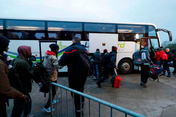 Migrants carry their belongings as they board a bus at the start of their evacuation and transfer to reception centers in France, and the dismantlement of the camp called the