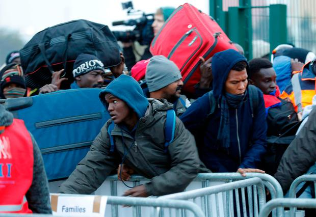Migrants with their belongings queue near barriers at the start of their evacuation and transfer to reception centers in France, and the dismantlement of the camp called the