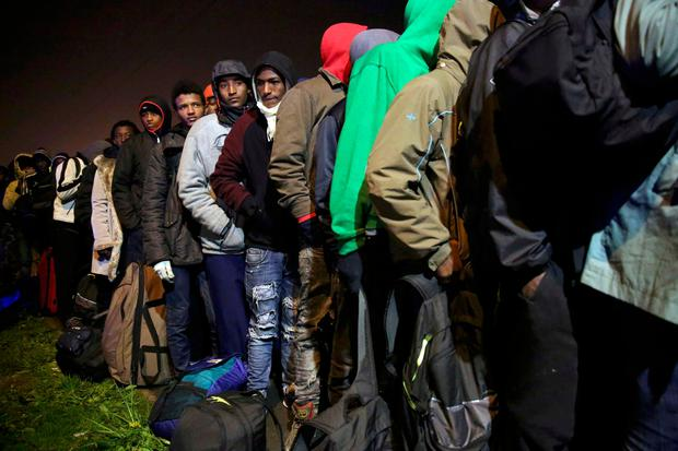 Migrants with their belongings queue at the start of their evacuation and transfer to reception centers in France, and the dismantlement of the camp called the