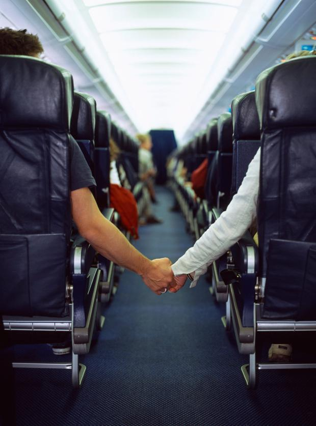 Couple holding hands across aisle of airplane
