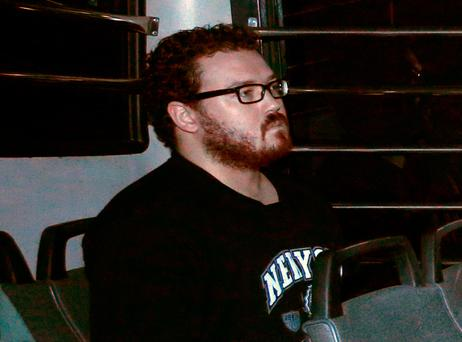 File photo of Rurik George Caton Jutting, a British banker charged with two counts of murder after police found the bodies of two women in his apartment, sitting in the back row of a prison bus as he arrives at the Eastern Law Courts in Hong Kong November 24, 2014. REUTERS/Bobby Yip/File Photo