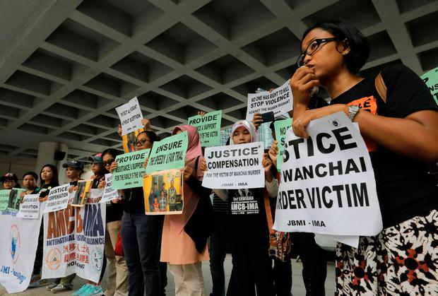 A migrant workers alliance group holds placards to protest the killings of two Indonesian women in 2014 outside the High Court in Hong Kong, Monday, Oct. 24, 2016. (AP Photo/Vincent Yu)