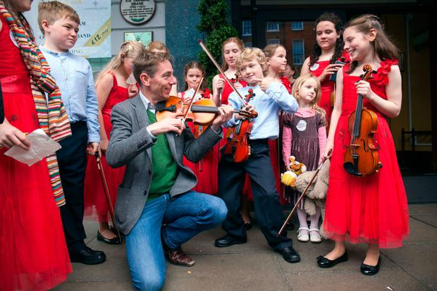 Christian Smith (8) teaches presenter Ryan Tubridy how to play the violin during the Cork auditions for RTÉ's 'Late Late Toy Show'. Photo: Clare Keogh